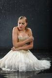 A menina bonita senta-se no assoalho, congela-se na chuva Fotografia de Stock Royalty Free