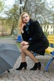 A menina bonita senta-se no banco no parque Imagens de Stock