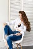 Menina bonita 'sexy' na camisa branca das calças de brim que senta-se em uma cadeira Cabelo longo lindo e jovem mulher encantador foto de stock