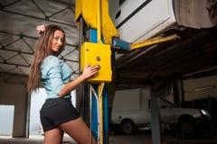 Menina bonita 'sexy' na loja de reparação de automóveis imagem de stock