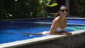 A menina bonita 'sexy' no biquini branco e em óculos de sol pretos está apreciando seu tempo na piscina A mulher nova está encont vídeos de arquivo