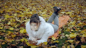 Menina bonita surpreendida olhando a tela do smartphone que encontra-se nas folhas caídas amarelas no parque do outono filme