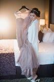 A menina bonita tenta sobre um vestido de casamento cor-de-rosa Imagens de Stock Royalty Free