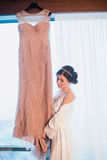 A menina bonita tenta sobre um vestido de casamento cor-de-rosa Fotos de Stock Royalty Free