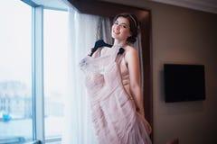 A menina bonita tenta sobre um vestido de casamento cor-de-rosa Fotografia de Stock
