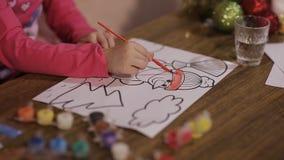 A menina bonita tira uma imagem de uma árvore de Natal e de um boneco de neve filme