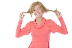 A menina bonita toca em seu cabelo. Fotografia de Stock