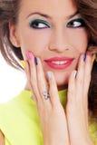 A menina bonita toca em sua cara com dedos coloridos fotografia de stock