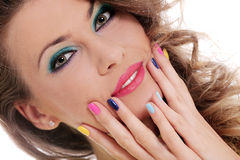 A menina bonita toca em sua cara com dedos coloridos Fotos de Stock