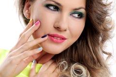 A menina bonita toca em sua cara com dedos coloridos Imagens de Stock Royalty Free