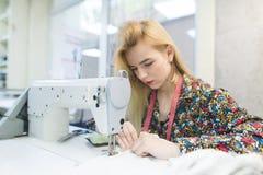 A menina bonita trabalha em uma máquina de costura A costureira cria o desgaste na máquina de costura Foco na máquina de costura fotografia de stock royalty free