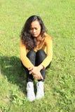 Menina bonita triste que senta-se na grama Fotos de Stock
