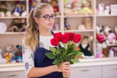 Menina bonita, um florista, escolhendo um ramalhete das flores imagem de stock royalty free