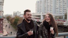 A menina bonita vem ao homem novo considerável são riso amigável do abraço alegremente, guardando o café afastado Imagens de Stock Royalty Free