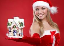 A menina bonita vestida como Santa prende um presente. fotos de stock royalty free
