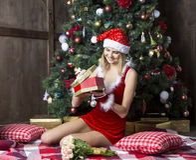 A menina bonita vestiu-se no terno de Santa perto da árvore de Natal imagem de stock royalty free