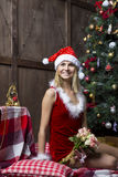 A menina bonita vestiu-se no terno de Santa perto da árvore de Natal imagens de stock