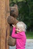 A menina bonito abraça o urso de madeira Imagem de Stock Royalty Free