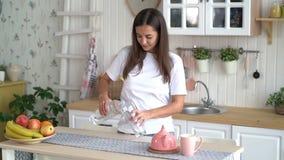 A menina bonito abre a garrafa e derrama a agua potável no vidro na cozinha, movimento lento vídeos de arquivo