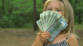 A menina bonito acena dólares na frente de sua cara video estoque