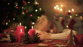 Menina bonito adormecido caído na tabela decorada para a celebração do Natal, casa acolhedor filme