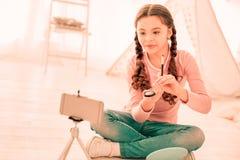 Menina bonito agradável que senta-se em sua sala imagem de stock