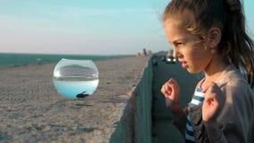 Menina bonito alegre que joga com um peixe pequeno no por do sol morno do verão do aquário pelo mar filme