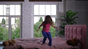 Menina bonito alegre que salta na cama no berçário