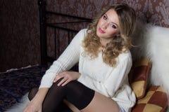 Menina bonito alegre 'sexy' bonita com um assento neve-branco do sorriso brilhante em uma camiseta morna e em peúgas na cama Fotos de Stock Royalty Free