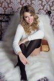 Menina bonito alegre 'sexy' bonita com um assento neve-branco do sorriso brilhante em uma camiseta morna e em peúgas na cama Fotos de Stock