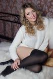 Menina bonito alegre 'sexy' bonita com um assento neve-branco do sorriso brilhante em uma camiseta morna e em peúgas na cama Imagens de Stock Royalty Free