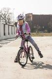 A menina bonito aprende montar uma bicicleta imagens de stock royalty free