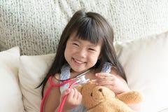 A menina bonito asiática é de sorriso e de jogo o doutor com stetho fotos de stock royalty free