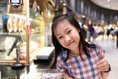Menina bonito asiática feliz e satisfeita na praça da alimentação na alameda, delici imagem de stock