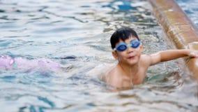 A menina bonito asiática pequena pratica nadar com seu irmão Família asiática video estoque