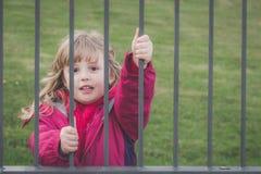 Menina bonito atrás das barras fotografia de stock royalty free