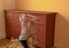 A menina bonito balança no cavalo de balanço Jogos e atos pequenos da menina como a princesa Foto de Stock