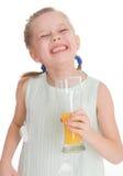 A menina bonito bebe o suco de laranja Fotografia de Stock Royalty Free