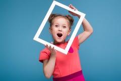 A menina bonito bonita no vestido cor-de-rosa guarda a moldura para retrato foto de stock