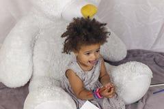 Menina bonito bonita que senta-se no tapete imagem de stock royalty free