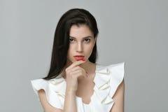 Menina bonito bonita que veste um vestido branco contra um backgro cinzento Foto de Stock
