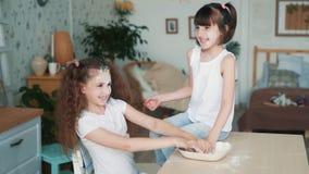 A menina bonito borra a cara da irmã com farinha, tem o tempo na cozinha, movimento lento do divertimento