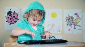 Menina bonito brincalhão que joga com teclado de computador e que olha a câmera video estoque