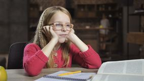Menina bonito cansado da escola com dificuldades de aprendizagem vídeos de arquivo