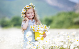 Menina bonito com as margaridas brancas da cubeta amarela imagem de stock royalty free