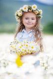 Menina bonito com as margaridas brancas da cubeta amarela imagens de stock