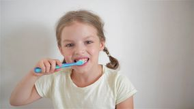 Menina bonito com as tranças que escovam diligently seus dentes Na mão da menina tem a escova de dentes azul cheerful filme