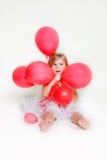 Menina bonito com balões vermelhos Fotos de Stock Royalty Free