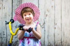 Menina bonito com a bicicleta contra o contexto de madeira Fotos de Stock Royalty Free