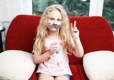 Menina bonito com bigodes de papel ao sentar-se na cadeira vermelha em casa Foto de Stock